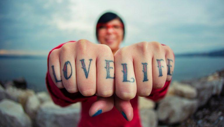 woman showing tattoos on knuckles that say love life