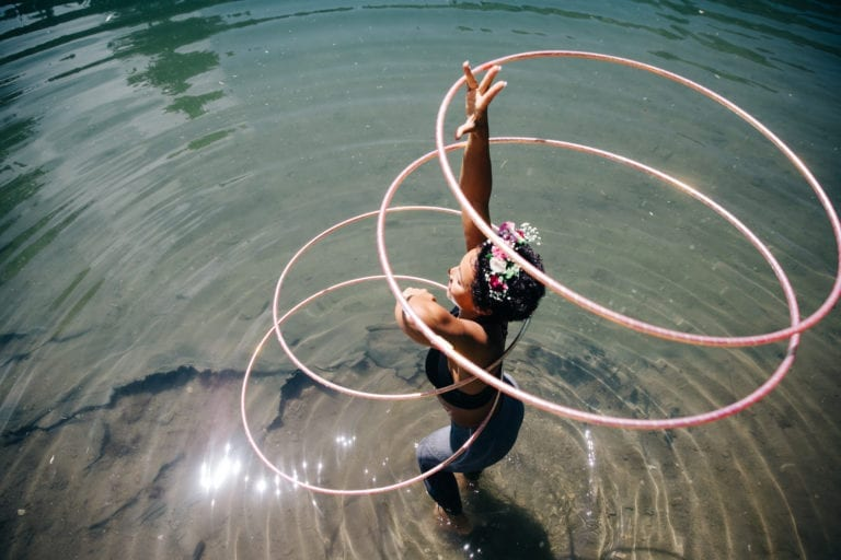 Girl hula hooping with three hoops in the water.