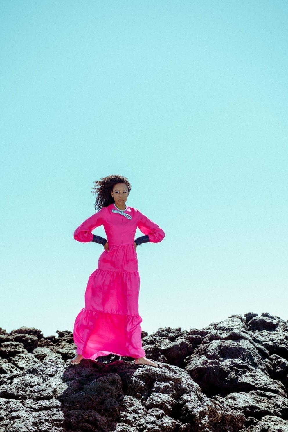 Corinne Bailey Rae in pink dress standing against blue sky on rocks