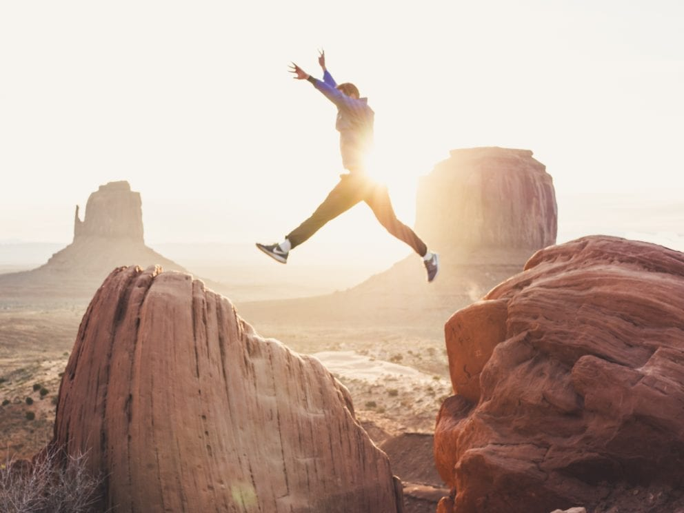 man jumping over two rocks with sun behind him