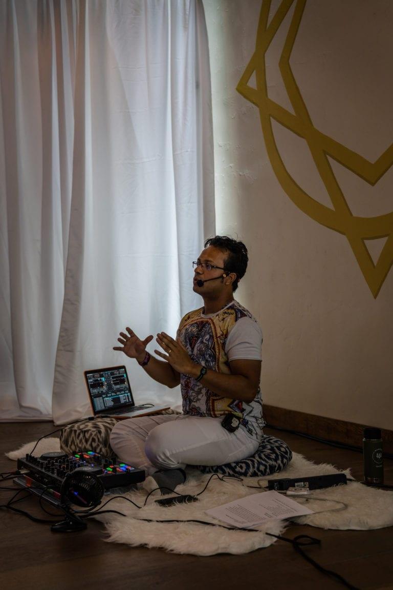 man sitting teaching with DJ equipment
