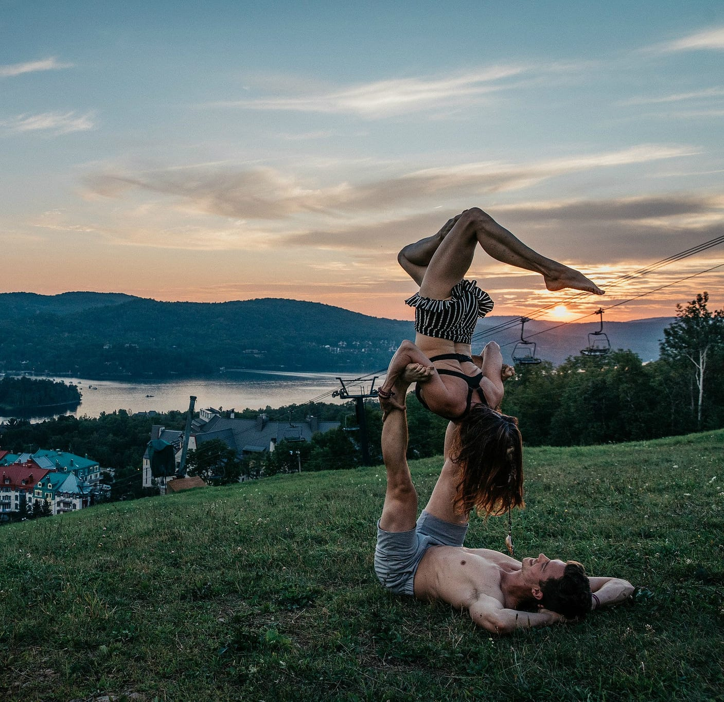 acro yoga on a mountain at sunset with village below
