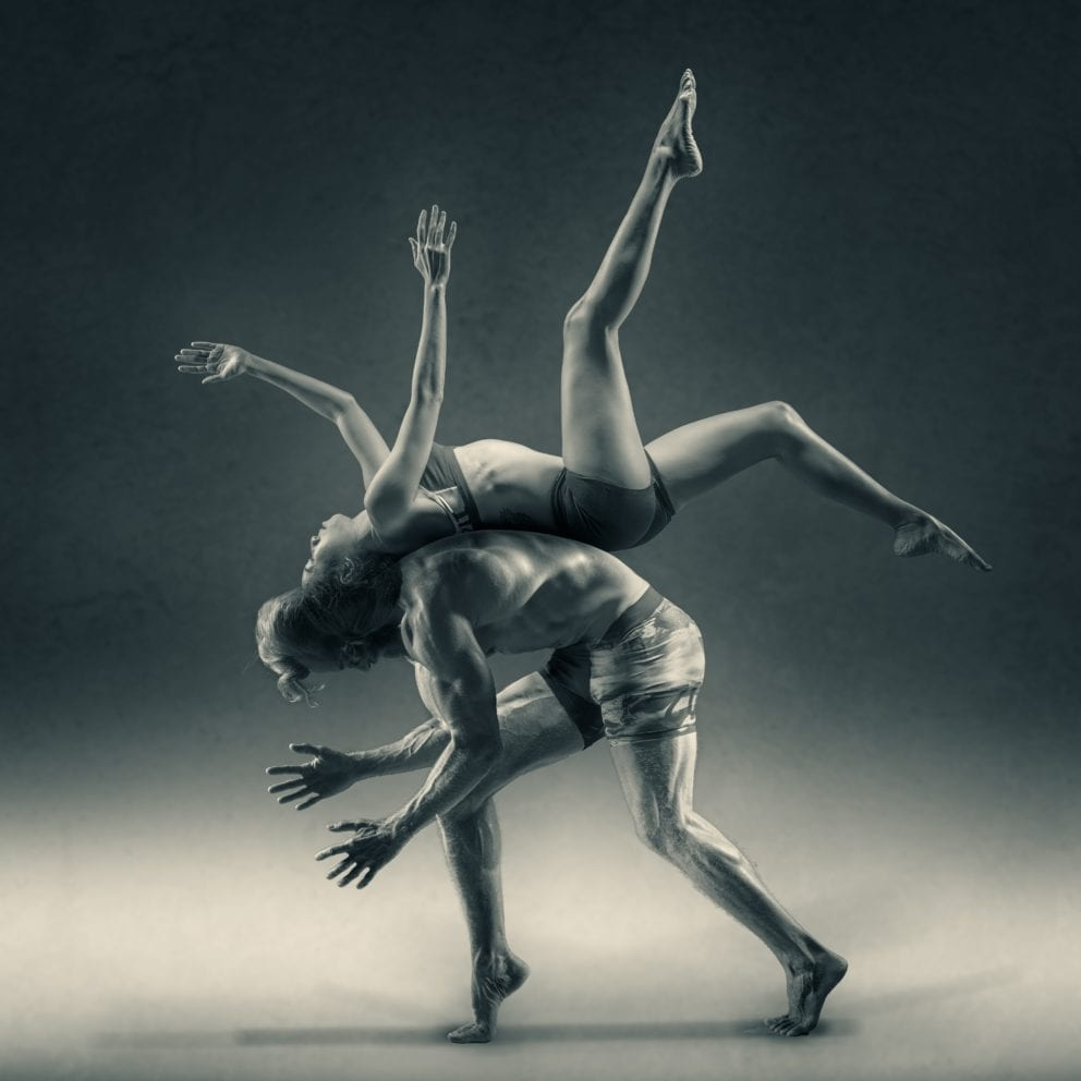 woman flipping over man yoga dance black and white