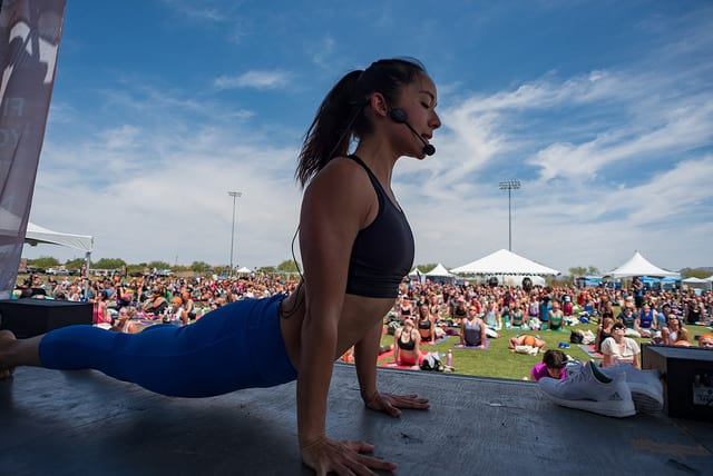 woman on stage teaching yoga to field of people