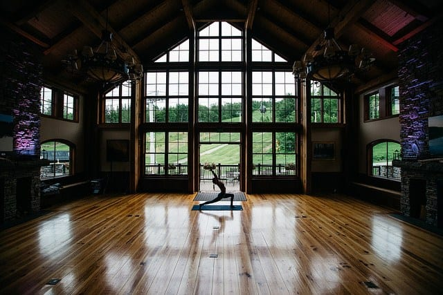 woman in high lunge in mountain lodge with large window