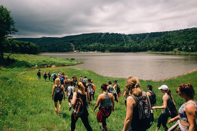 people hiking around lake in green mountain