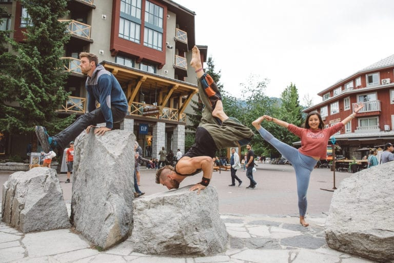 Friends practicing yoga in the village square in Whisler, Canada.
