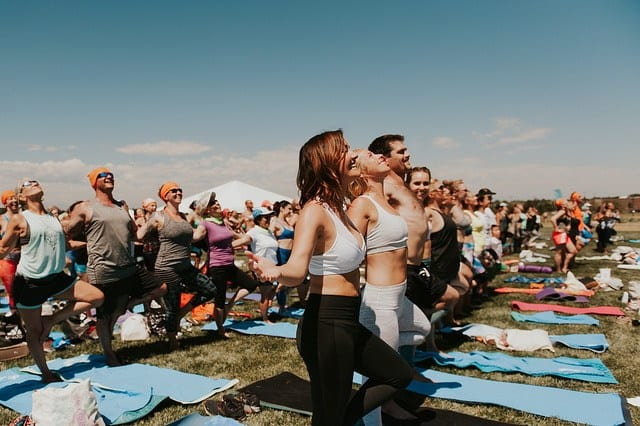 people in crowd doing supported tree pose at yoga festival in denver