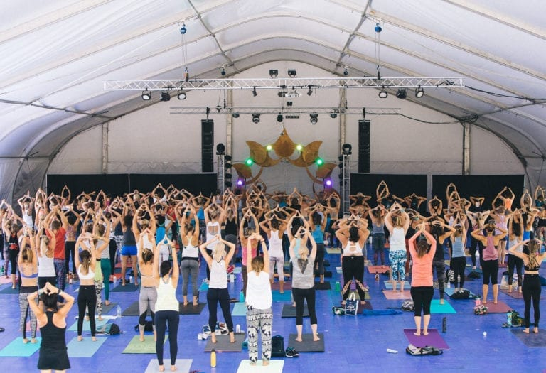 large group of people doing yoga with arms raised in tent