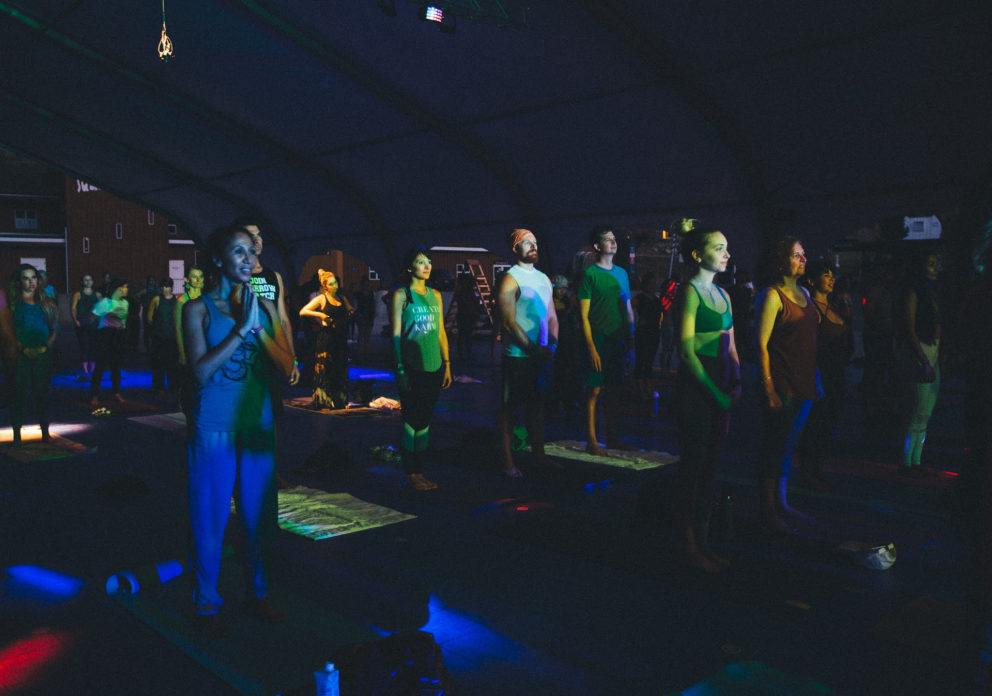 people in dark room with rainbow lights practicing Kundalini yoga