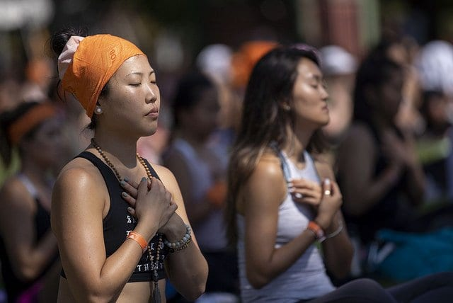 people meditating in field at yoga festival
