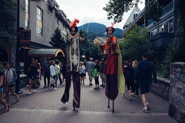 marching band on stilts walking through mountain town