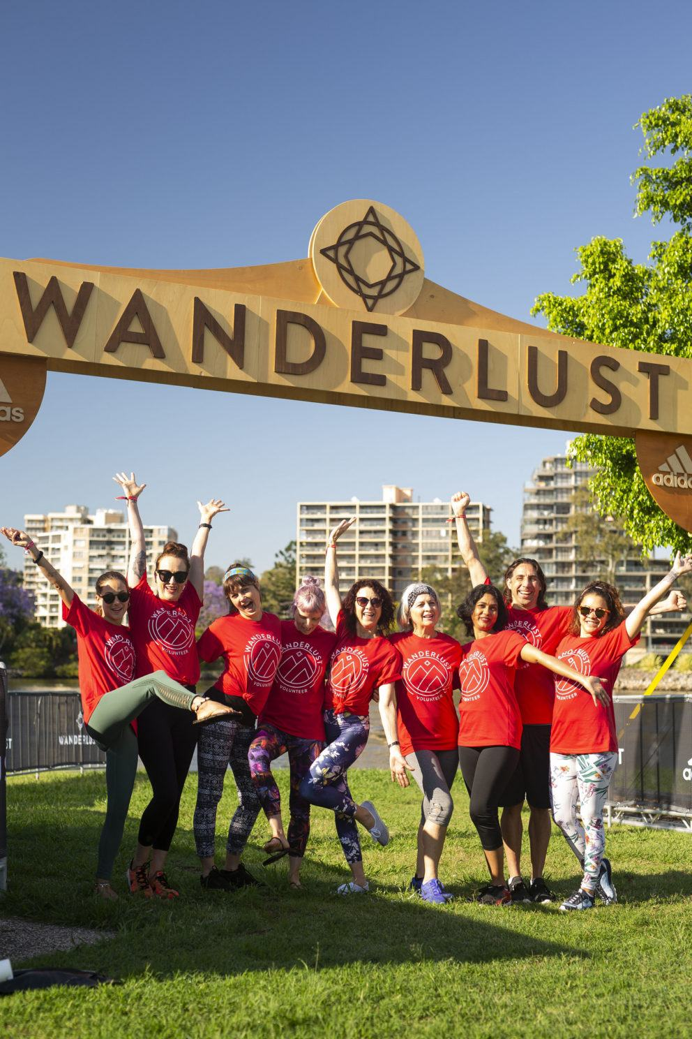 group of people in red shirts under Wanderlust arch
