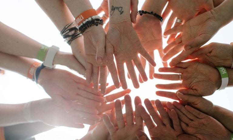 People's hands stacked on top of each other in a circle with sunlight in the background.
