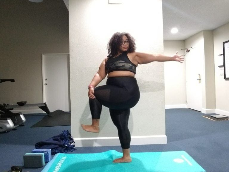 woman in tree pose against wall on turquoise yoga mat