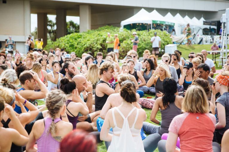 large group of yogis with hands in Anjali mudra