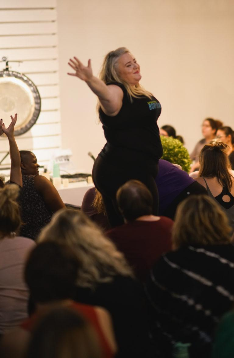 woman standing with arms raised in workshop with gong