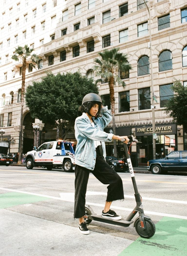 woman on scooter riding through city