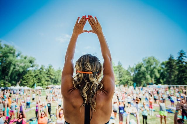 chelsey korus on stage with arms raised large scale yoga class