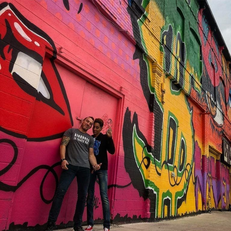 Derek Cook and DJ Seriousblack by graffiti wall