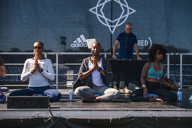 3 teachers sitting on stage at yoga festival