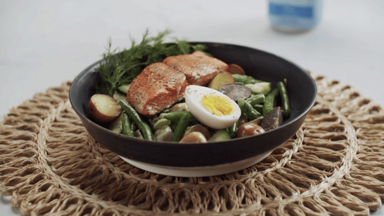 bowl with salmon, egg, and green beans on a table.