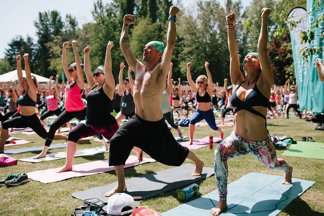 people practicing yoga in large group at festival