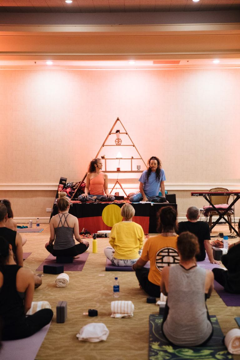 yoga teachers on stage teaching with triangle altar behind them