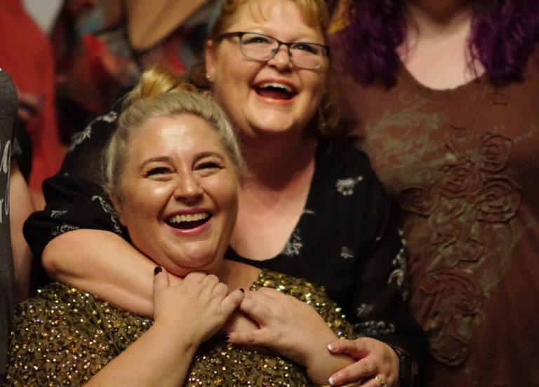 women hugging looking at camera laughing