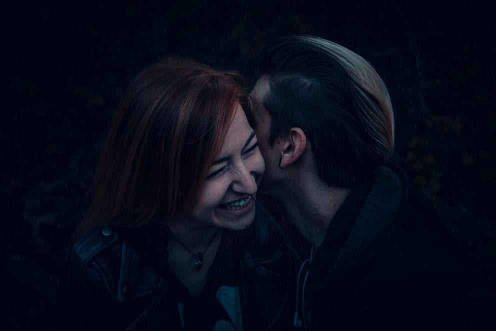 man and woman kissing on black background