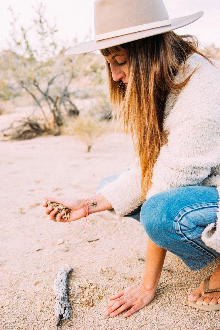woman bending down picking up something in desert